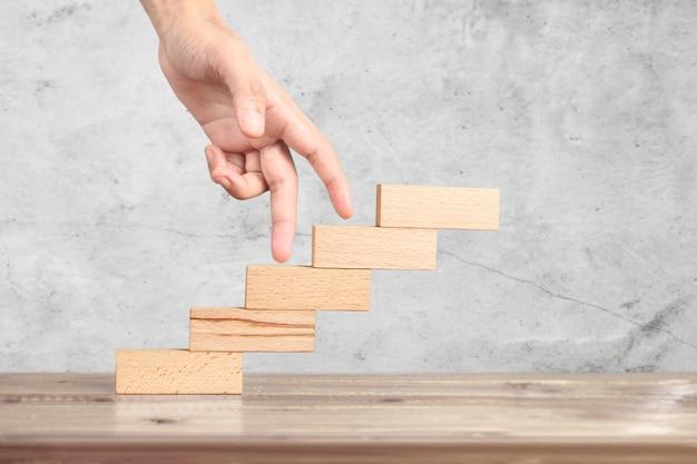A mão compara a pessoa que intensifica o bloco de madeira que empilha como a escada da etapa