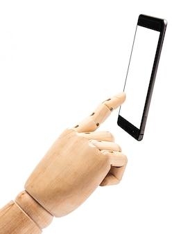 A mão da boneca de madeira faz os dedos para tocar com o telefone esperto no fundo branco