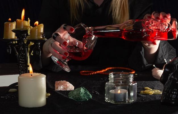 A mão da bruxa segura uma garrafa com um líquido vermelho na forma de uma caveira e um copo