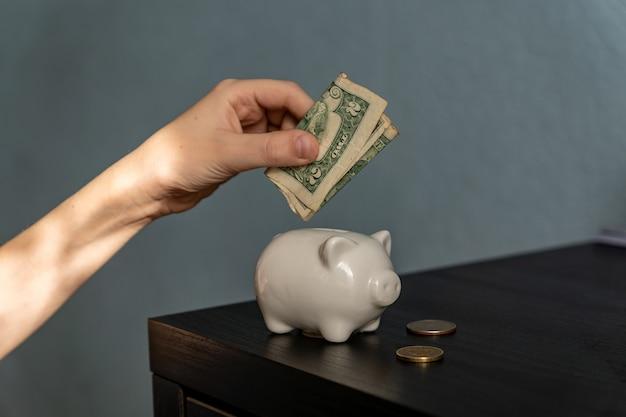 A mão da criança colocando um dólar americano em um cofrinho. conceito de poupança infantil. serviços bancários para crianças.