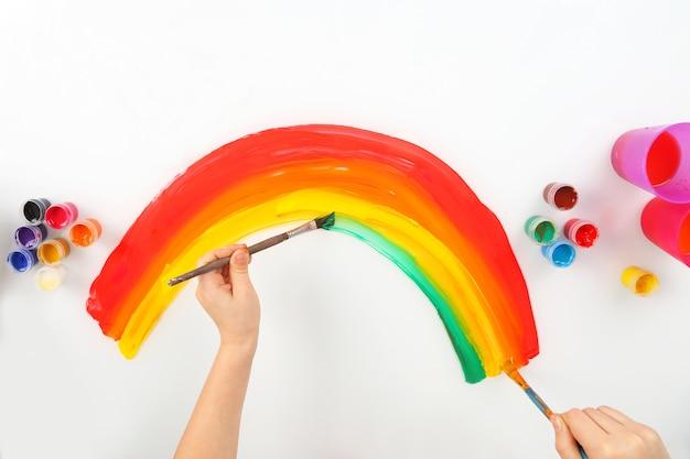 A mão da criança desenha um arco-íris em um branco