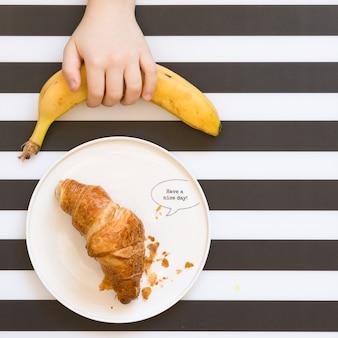 A mão da criança pega uma banana orgânica da mesa vista de cima croissant francês em um prato branco