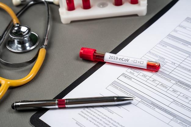 A mão da enfermeira preenche um teste de coronavírus de formulário médico na mesa do hospital com máscara respiratória e tubos de ensaio com sangue para análise. infecção pelo vírus 2019-ncov originária de wuhan, china