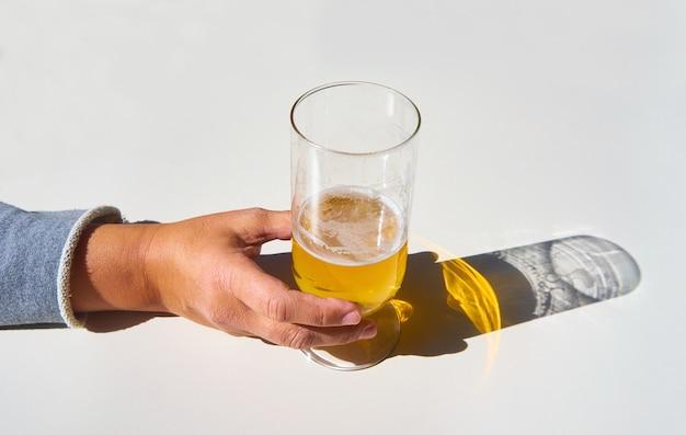 A mão da fêmea pega um copo de cerveja com a sombra refletida na mesa branca
