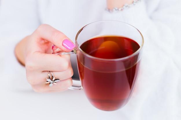 A mão da garota close-up com um lindo anel e manicure que segura uma xícara transparente de chá