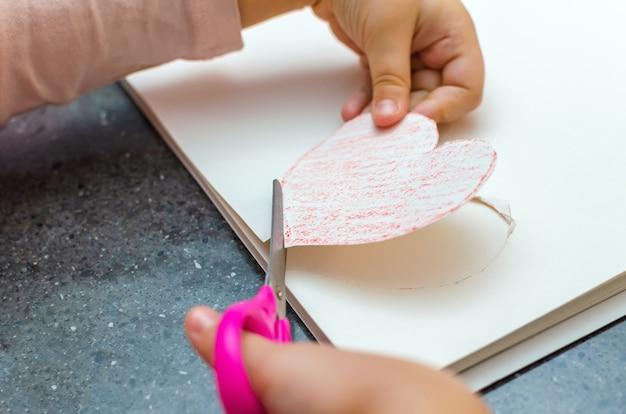 A mão da garota segura um coração cortado de papel. criatividade infantil - desenhos e artesanato para o dia dos namorados ou dia das mães.
