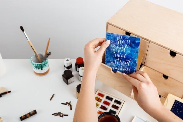 A mão da garota segurando o cartão postal com palavras estrelas não podem brilhar sem escuridão.
