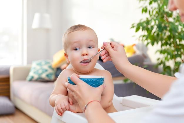 A mão da mãe alimenta o bebê loiro feliz fofo engraçado com a colher da tigela azul, plano de fundo do apartamento, espaço de cópia, horizontal