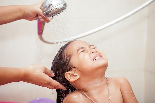 A mão da mãe derrama água do banho para lavar o cabelo da menina
