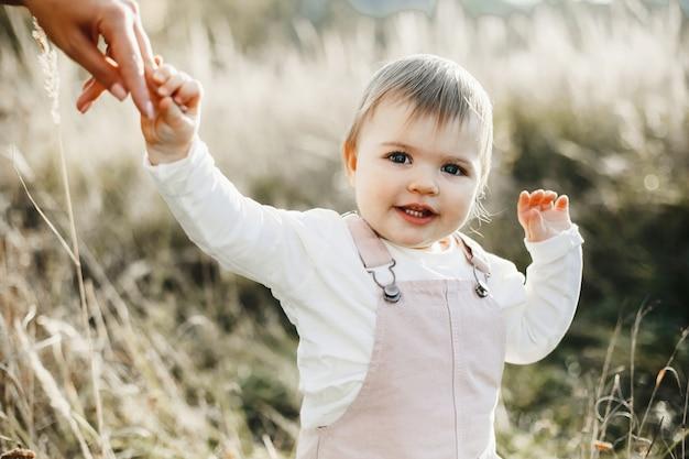 A mão da mãe segura sua filha para a mão
