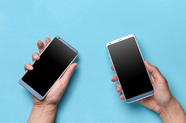 A mão da menina e do homem segura telefones celulares modernos sobre um fundo azul, com espaço de cópia para o texto. postura plana