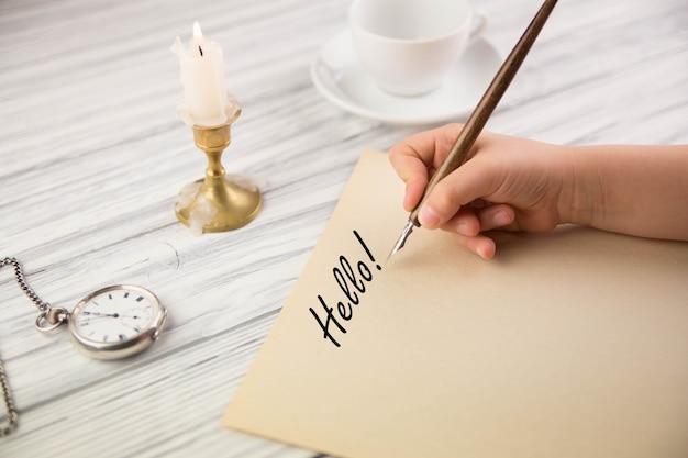 A mão da menina escreve com o antigo cabo no papel