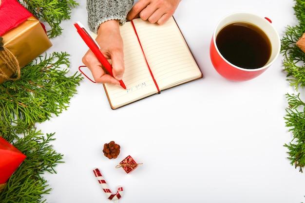 A mão da menina escreve os desejos de ano novo. menina escreve caneta em um pedaço de papel desejos de natal.