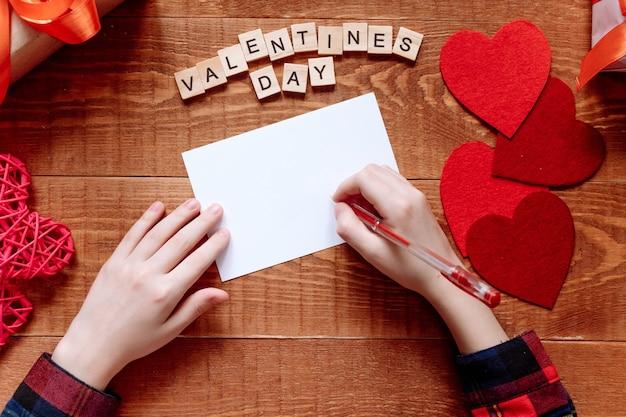 A mão da menina escreve uma carta de amor. dia dos namorados. cartão feito à mão com um coração vermelho em forma de figura. 14 de fevereiro é uma celebração de celebração. vista de cima