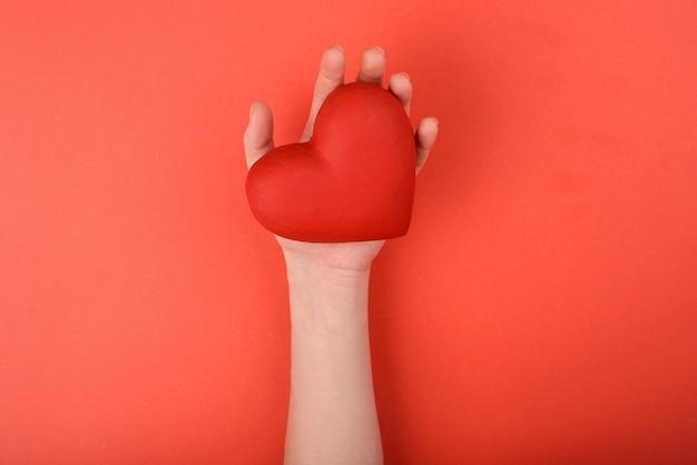 A mão da menina que prende um coração vermelho em um fundo vermelho. dia dos namorados.