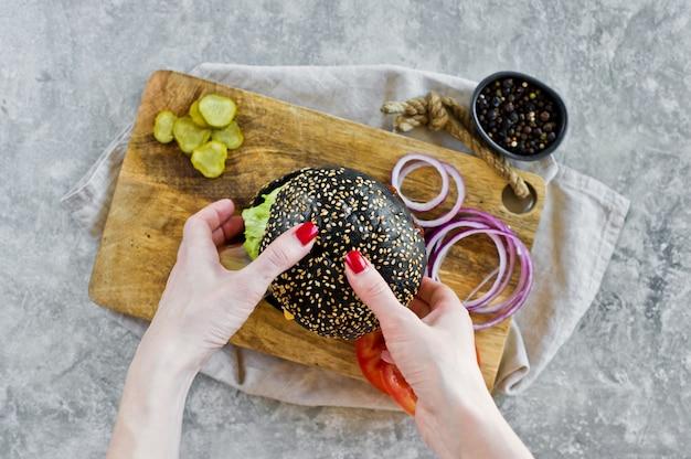 A mão da menina que prende um hamburguer preto.
