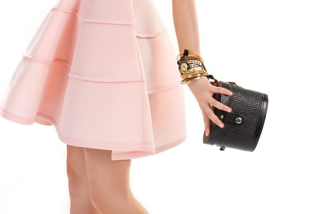 A mão da menina segura a bolsa preta. relógio de pulso e bolsa pequena. vestido salmão e acessórios clássicos. pulseiras de ouro caras.