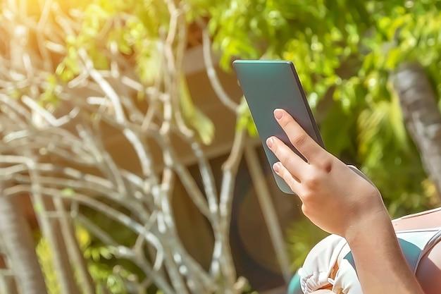 A mão da menina segura um e-book azul-marinho contra o pano de fundo de árvores verdes no verão