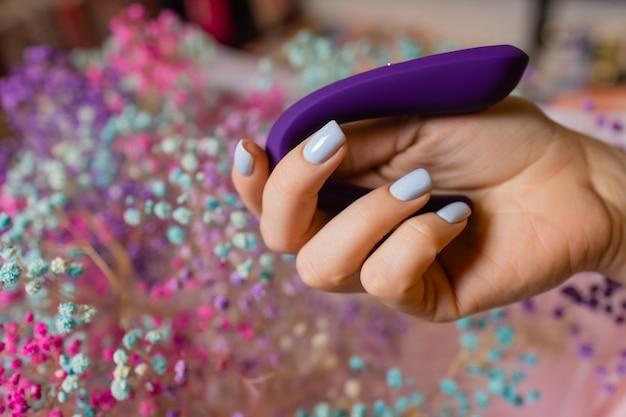 A mão da menina segura um massageador para sexo. vibrador para masturbação. dildo para estimulação vaginal e clitoriana. imagem para sex shop.