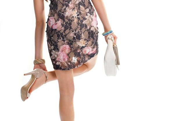 A mão da menina toca seu sapato. vestido preto com estampa rosa. bolsa de couro de qualidade. acima de tudo, beleza.