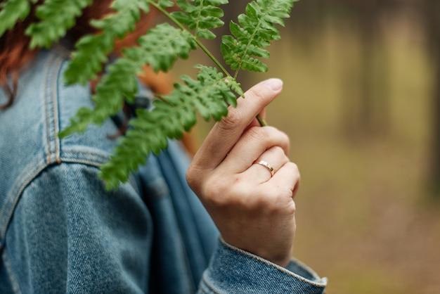 A mão da menina tocando a folha de samambaia. macro. tema floresta, cores da moda, bokeh forte