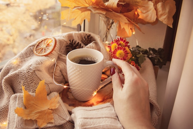 A mão da mulher alcança sua caneca de café. rodeado de suéteres e decoração de outono