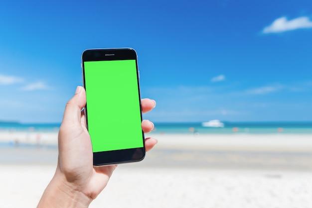 A mão da mulher bonita usando o telefone esperto na praia.