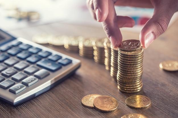 A mão da mulher colocou moedas de euro com um efeito de crescimento. natureza morta com cackulator de plano de negócios e moeda de euro.