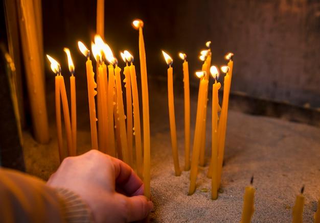 A mão da mulher colocou uma vela de cera na chama para rezar na igreja. velas de cera de abelha queimam no templo