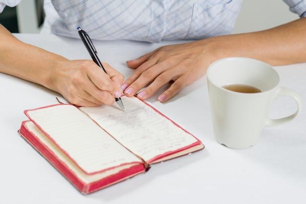 A mão da mulher com caneta escreve em seu diário