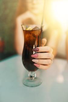 A mão da mulher com manicure rosa e roxa segura o copo com a garota coquetel no bar de verão goza de dr ...
