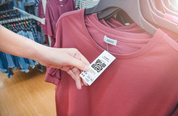 A mão da mulher com uma etiqueta da etiqueta do cair de pano com código de qr em uma loja da roupa.