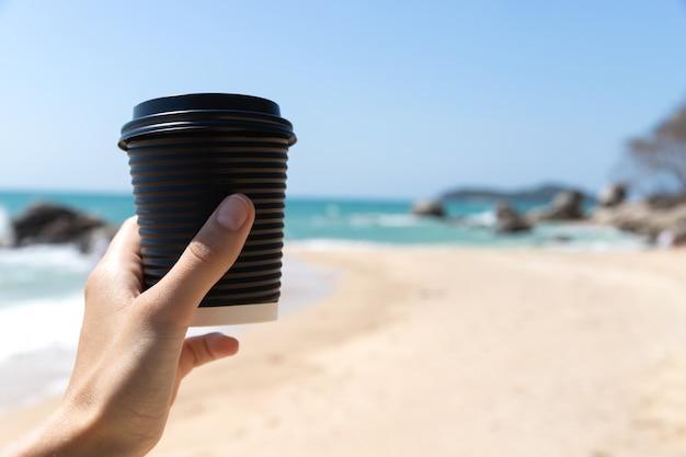 A mão da mulher com uma xícara de café de papel cartão de chá à beira-mar.