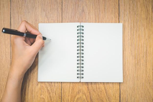 A mão da mulher da vista superior está escrevendo em um bloco de notas vazio com uma pena no fundo de madeira.
