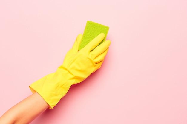 A mão da mulher de limpeza em uma parede rosa. conceito de limpeza ou limpeza