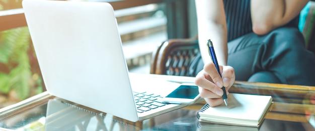 A mão da mulher de negócio está escrevendo em um bloco de notas com uma pena e está usando um computador portátil.