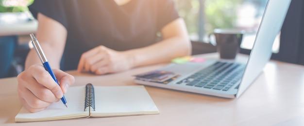 A mão da mulher de negócio está escrevendo em um bloco de notas com uma pena.