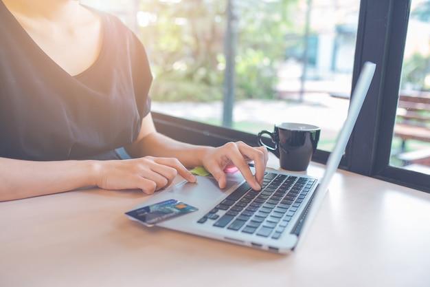 A mão da mulher de negócio está usando um computador portátil no escritório. na tabela há um cartão de crédito.