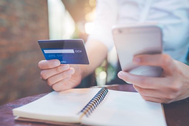 A mão da mulher de negócio prende um cartão de crédito azul e usa telefones móveis.