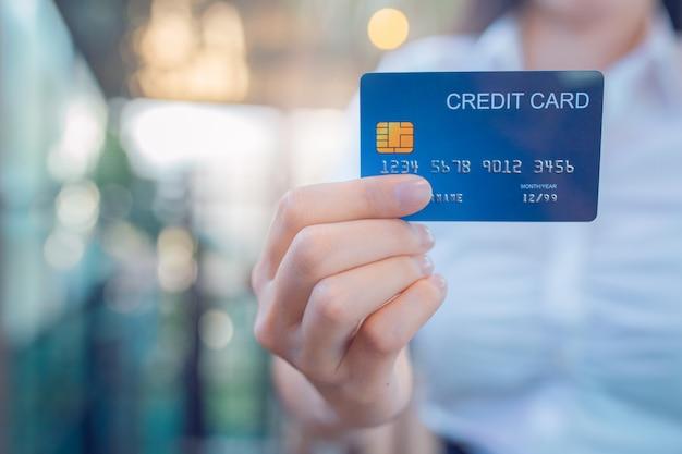 A mão da mulher de negócio prende um cartão de crédito azul.