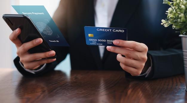 A mão da mulher de negócios que guarda o cartão de crédito e o smartphone comunicam o pagamento seguro.