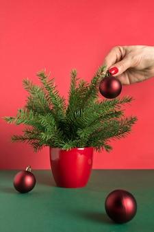 A mão da mulher decora uma pequena árvore de natal com bolas vermelhas.