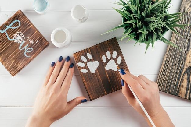 A mão da mulher desenha impressões de patas em um quadro decorativo feito de madeira queimada com pincel de tinta branca, faça você mesmo criativo