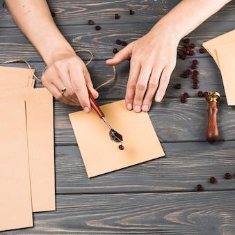 A mão da mulher do close-up que derrama a cera do derretimento sobre o envelope no fundo de madeira da textura