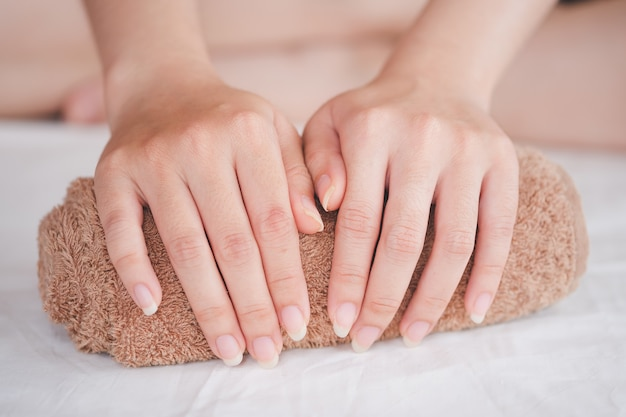 A mão da mulher é colocada na toalha de rolo, conceito de cuidados de saúde da unha.