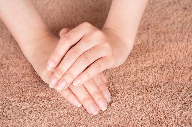 A mão da mulher é colocada sobre a toalha, no conceito de cuidado com a saúde da unha.