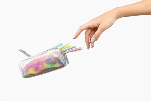 A mão da mulher e os artigos de papelaria levitam sobre fundo branco