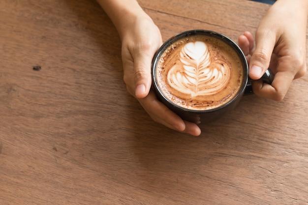 A mão da mulher é segurando a arte piccolo latte em uma xícara de arte bonita do coração do leite
