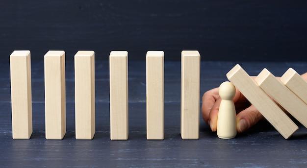 A mão da mulher entre os blocos de madeira evita que a maior parte dele caia
