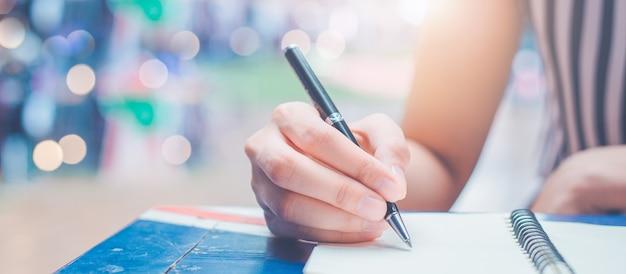 A mão da mulher está escrevendo em um bloco de notas em branco com uma caneta em uma mesa de madeira.